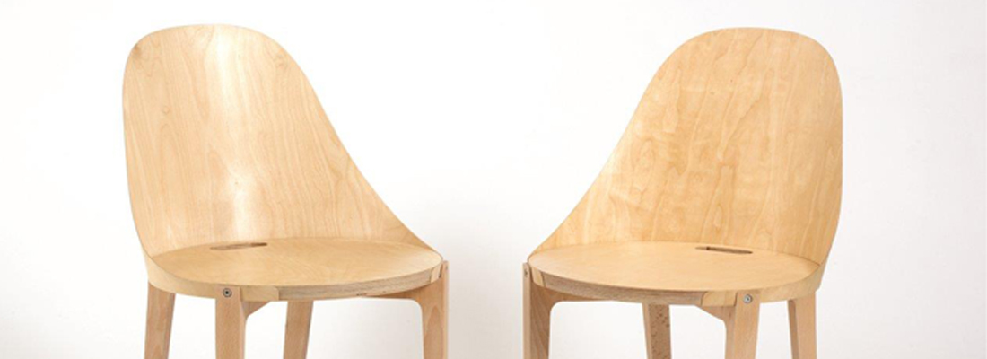 Two wooden dining chairs, simple in design with a round seat and full shaped back.