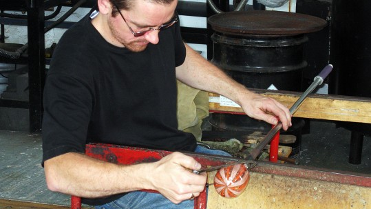 A young man sits and forms a small round object by spinning the hot glass.