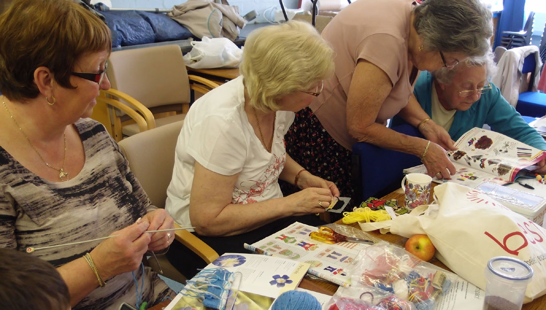 A group of older ladies learn how to knit from various books.