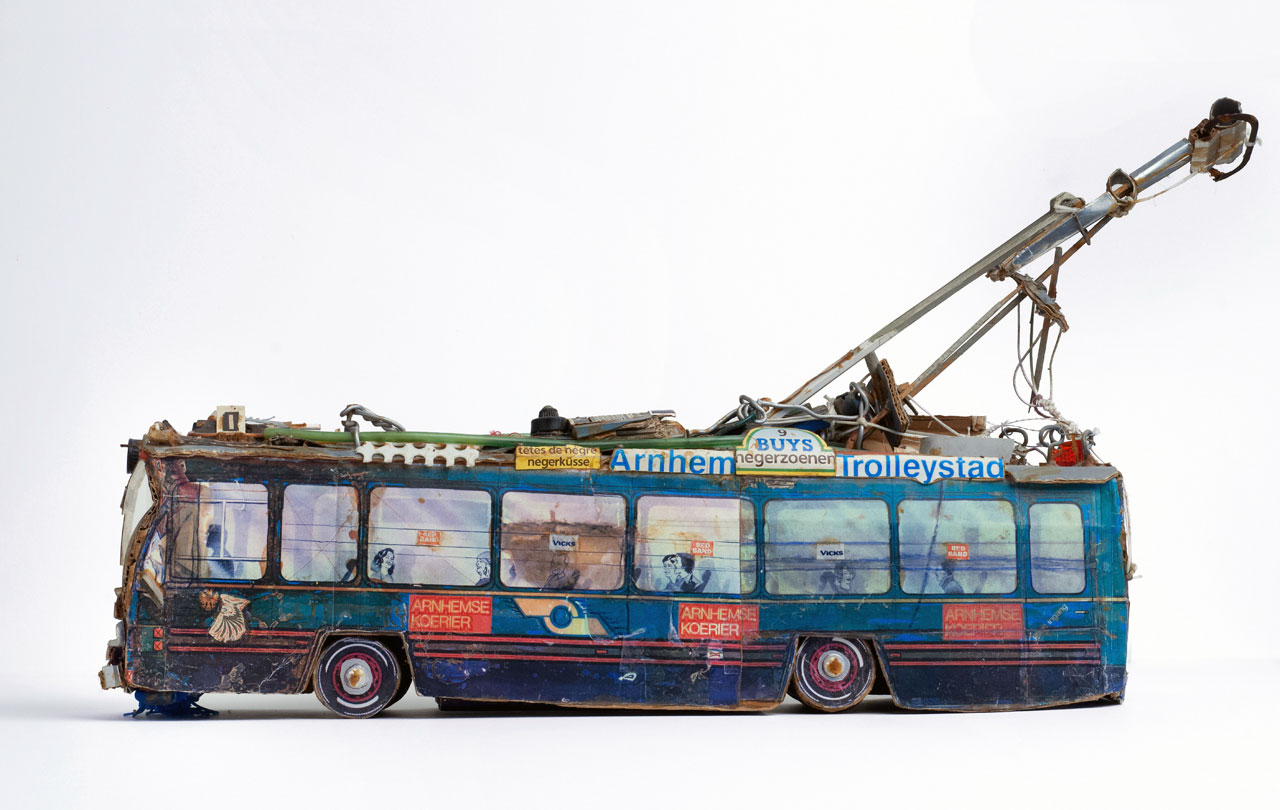 A small model of a tram made out of found materials such as cardboard packaging.