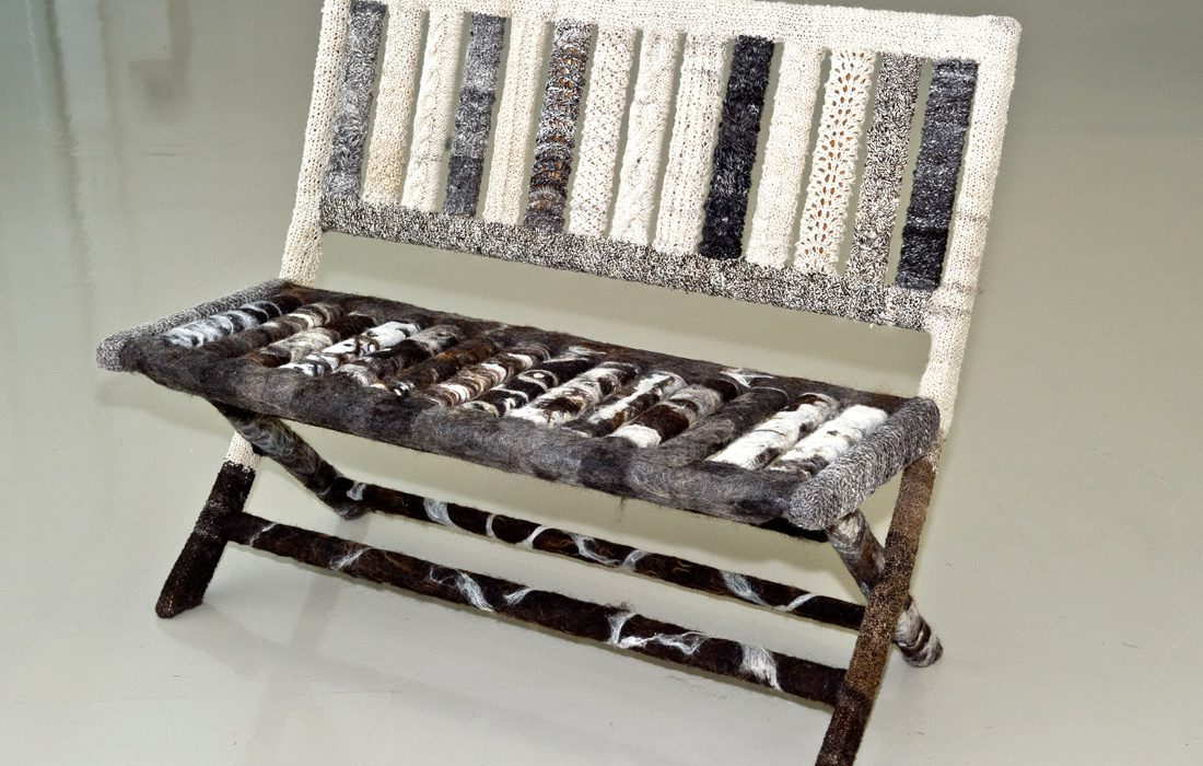 A bench covered in patterned woollen pieces of various cream, grey and brown colours.