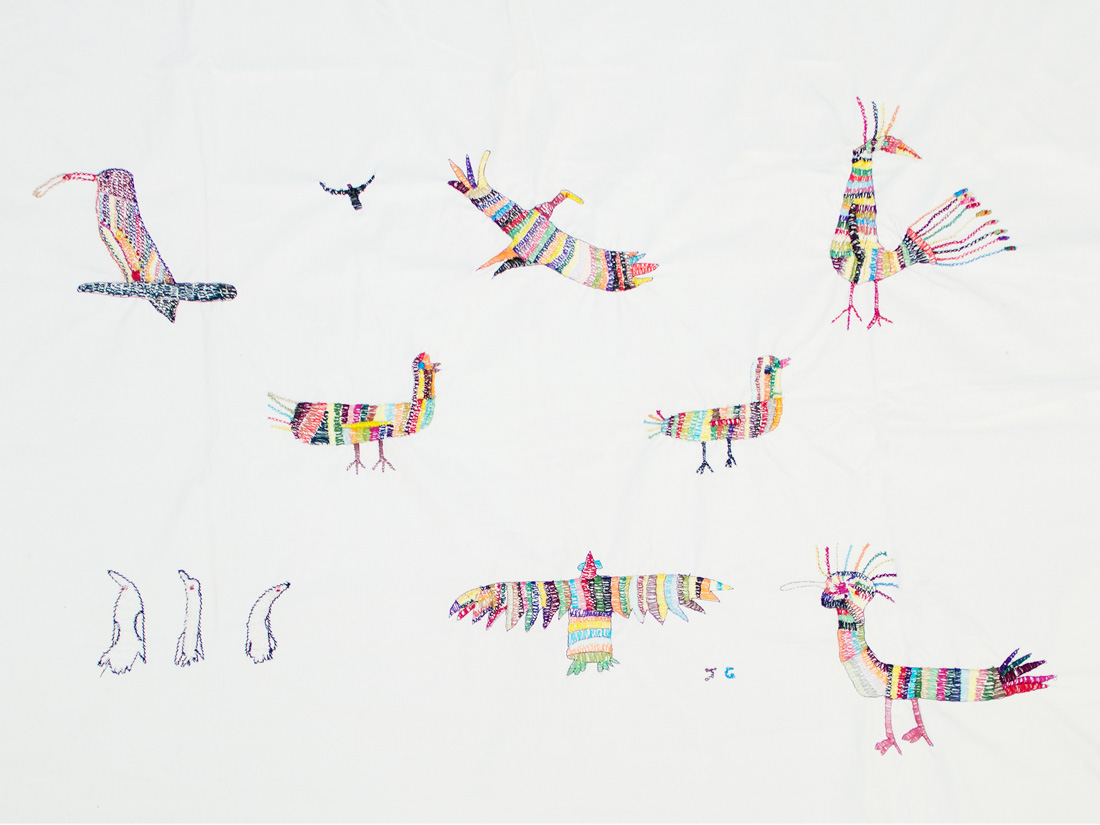 a white sheet is embroidered with small colourful birds. the style is quite naive.