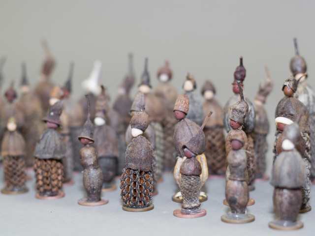 Lots of tiny figures standing in rows made from nuts and seeds.