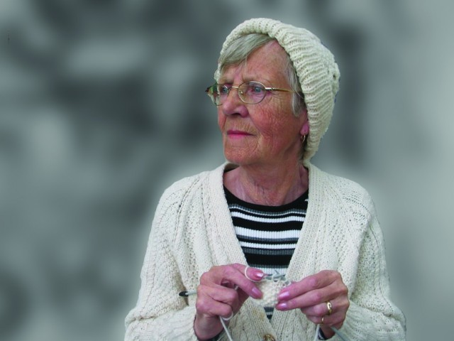 older lady wearing knitted hat and cardigan and knitting
