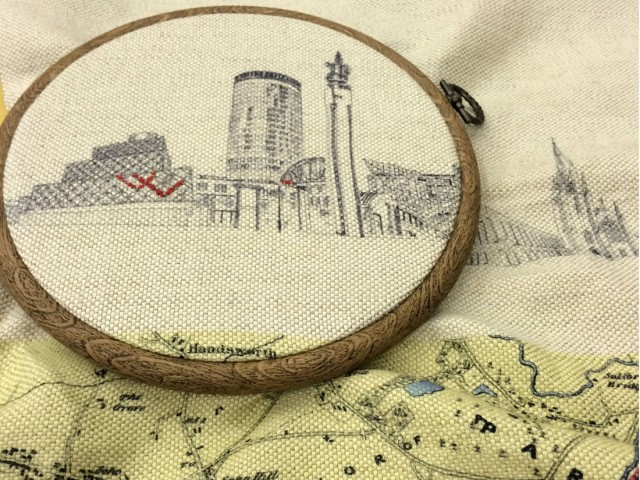 embroidery hoop with printed design of Birmingham city skyline with some parts sewn in red thread
