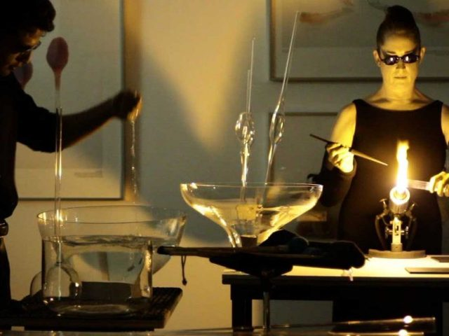 Inside a gallery a woman is performing with tools and glass, there is a large flame, other galss vesssels are filled with water.