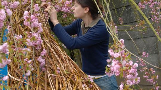 An artist weaves flowers into a willow sculpture.