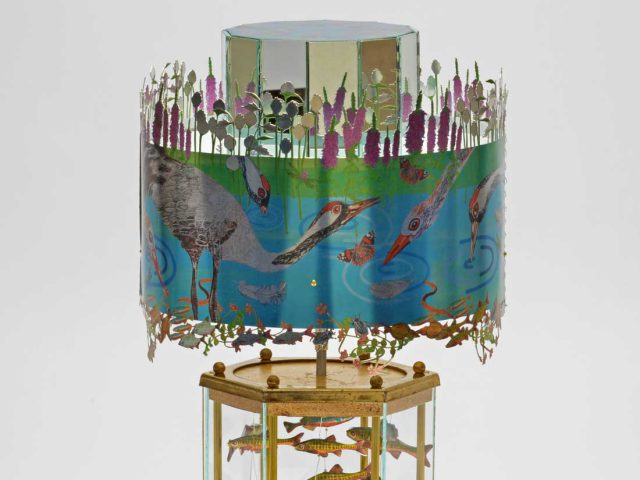 A highly decorated praxinoscope with wildlife scenes including birds, plants and fish.