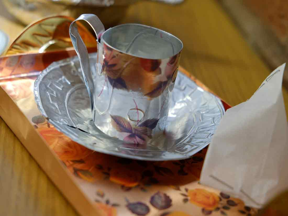 A tea cup with a handle adn a small tray shaped from thin metal that has been printed with flowers and marked with indentations.