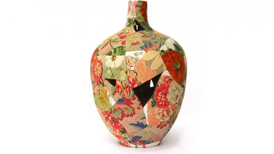A vase is reformed frmo broken pieces covered in bright fabric and stiched back together.