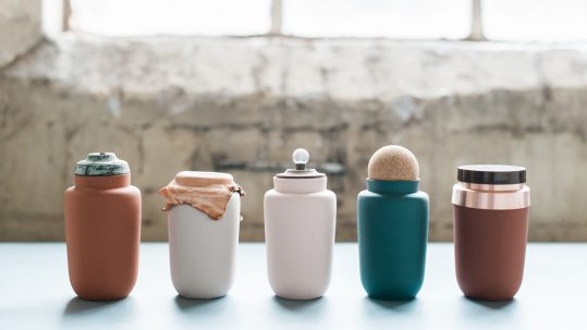 A row of simple shaped ceramic vessels with additions of found objects such as lids and cloth covers.