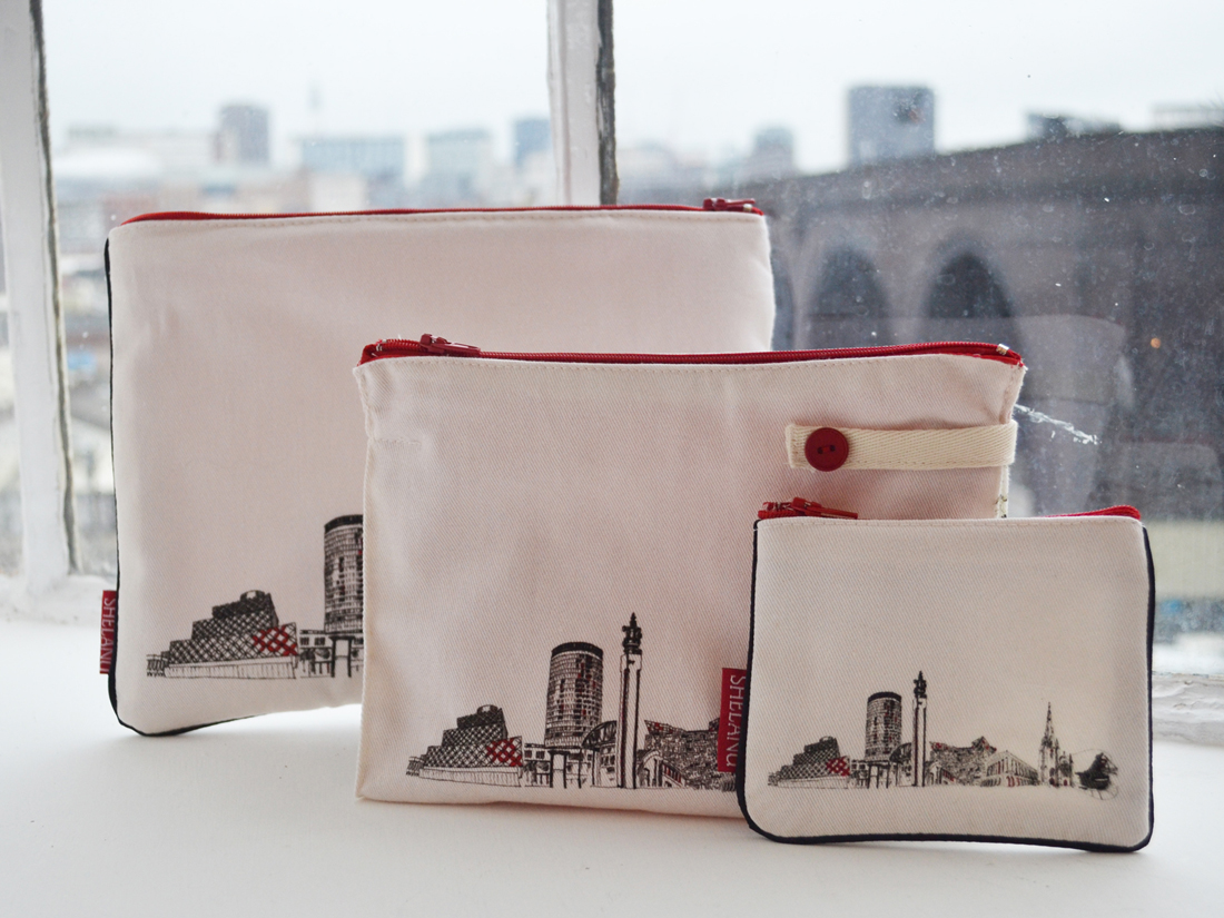 The i pad case, wash bag and purse sit on a windowsill. They are simple in design with a black and white line drawing of the skyline and red trimmings.