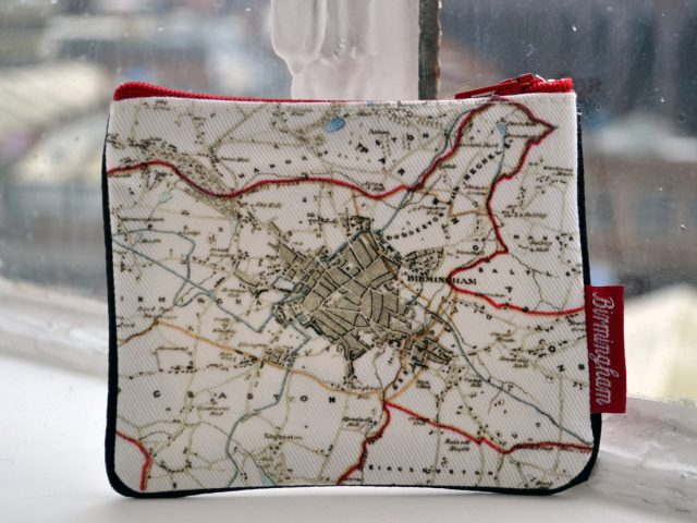 The purse sits on a windowsill. It is simple in design with an old map of birmingham printed onto it and red trimmings.The tag says 'birmingham'.