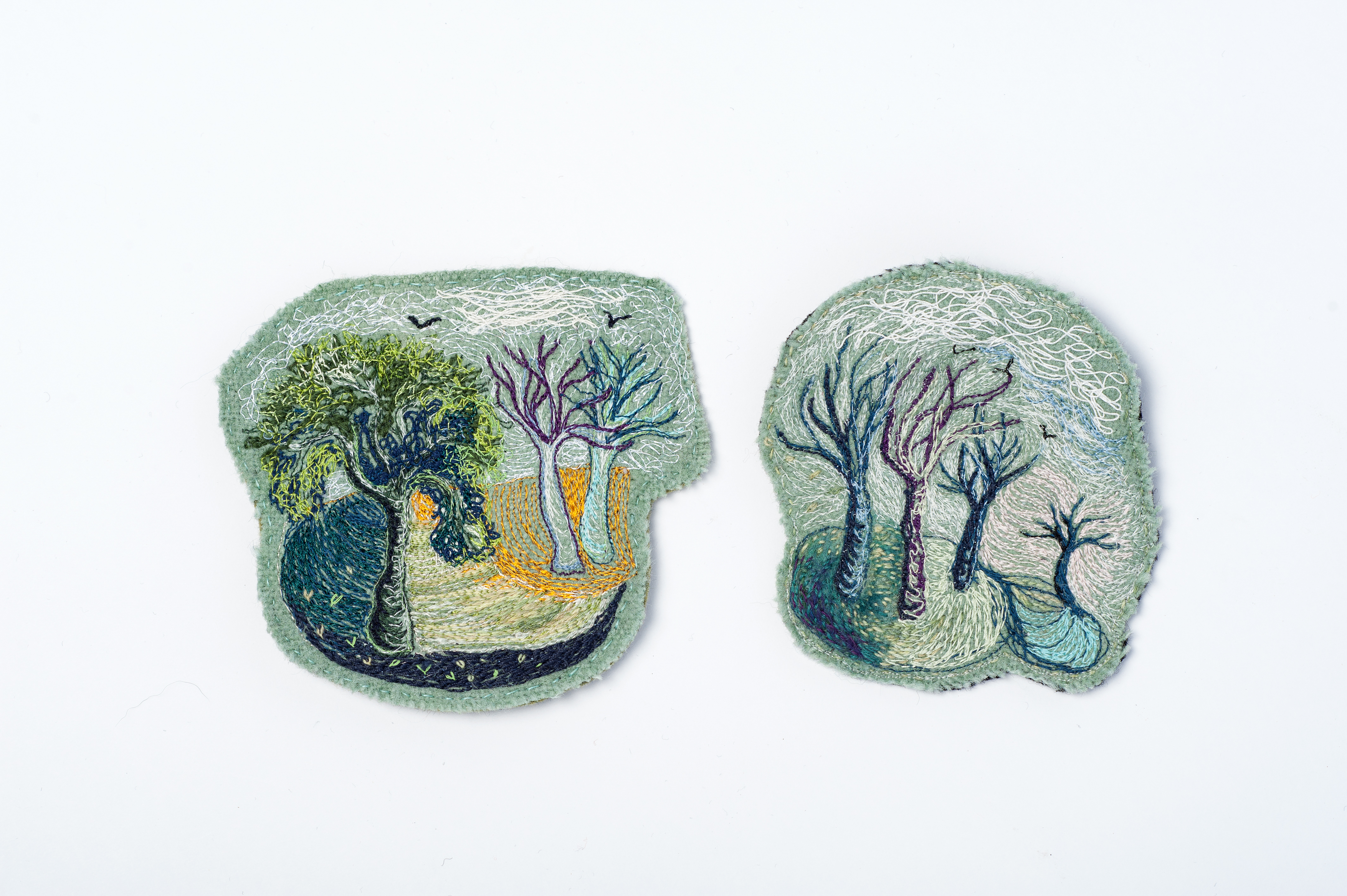 Two small flat pieces are heavily embroidered with imags of trees which look like they are blowing in the wind.