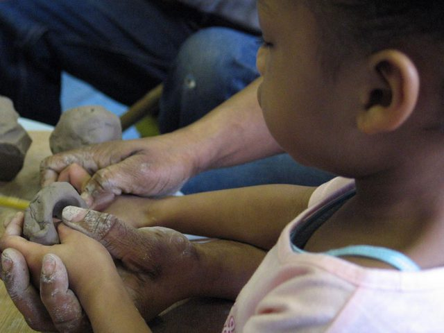 A small boy holds a pices of wet clay and pushes his fingers into it to make a small pot. The image shows adult hands working with the childs hands.