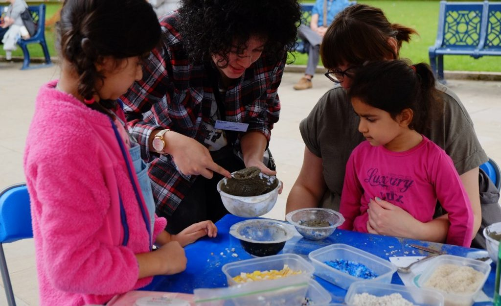 A young woman is scooping wet concrete out of a bowl into a smaller bowl using a spoon as a mother and her two young daughters watch