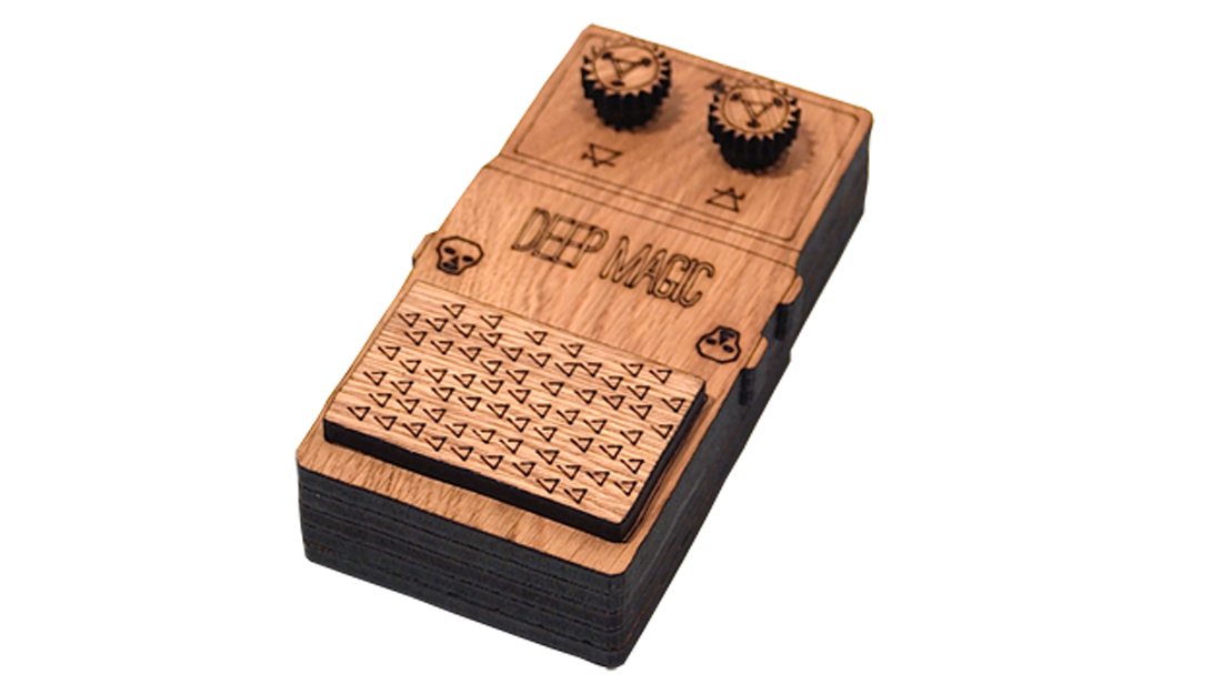 A laser cut model of a guitar pedal showing the words deep magic.