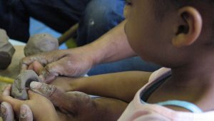 A small child and an adult hold a piece of wet clay and mould it together.