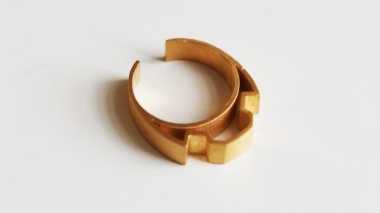 a gold ring with a very geometric design