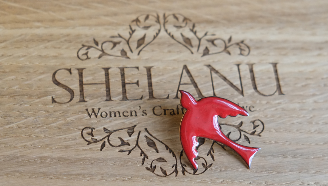 red enameled bird brooch. simple in design.