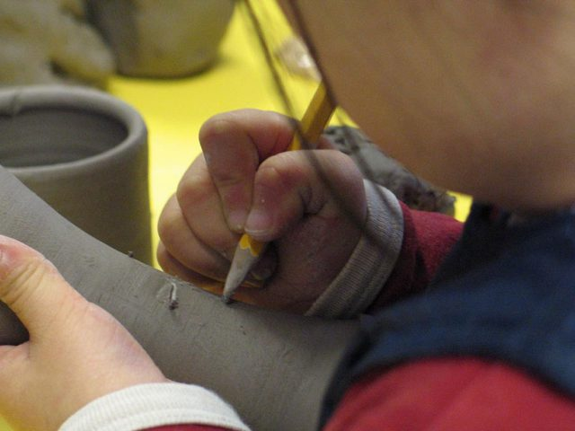 A very young child makes marks in clay using a pencil.