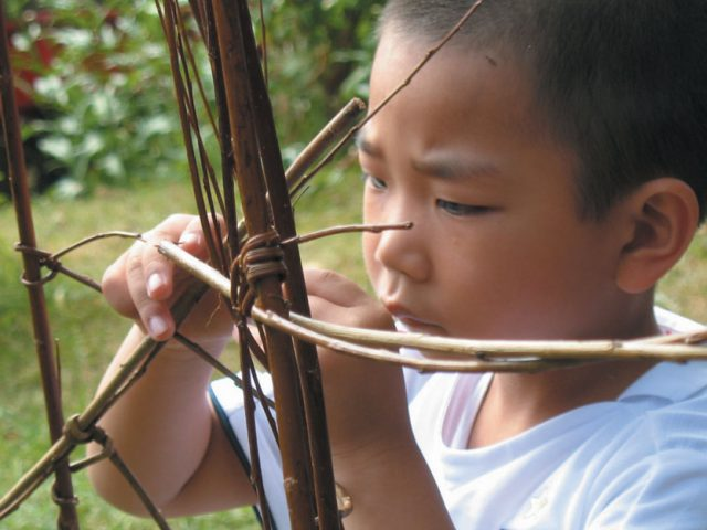 A young boy concentrates on joining two pieces of willow together.