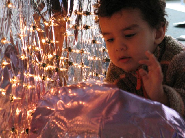 A young child crawls through a tunnel of lights and reflective fabrics.