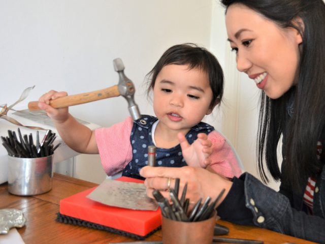A woman and a young girl sit a a table covered in tools. The young girl, aged about 2, uses a hammer to punch some metal.