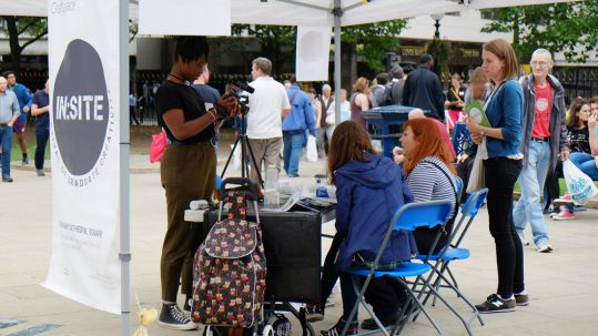 Two young women are sat at a table and are being filmed by another young woman, whilst a four young woman watches. They are underneath a large tent and there is a busy public square in the background