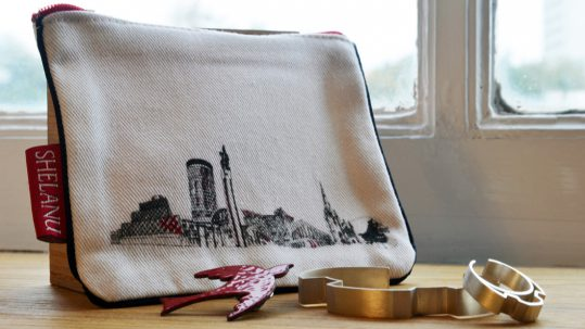Shelanu products: A purse with a line drawing of Birmingham, a red bird brooch and a silver bracelet.