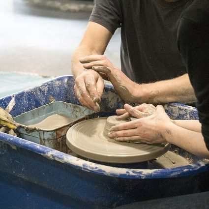 Hands working together at the potters wheel.