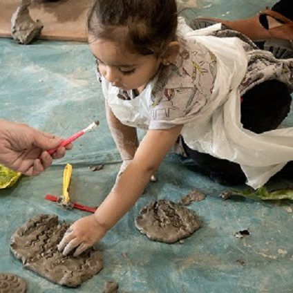 A young girl presses her fingers into wet clay.