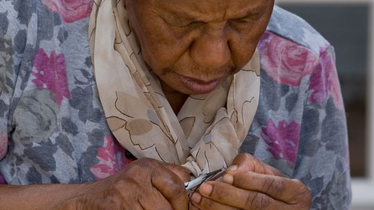 An older woman concentrates on making jewellery with some small tools.