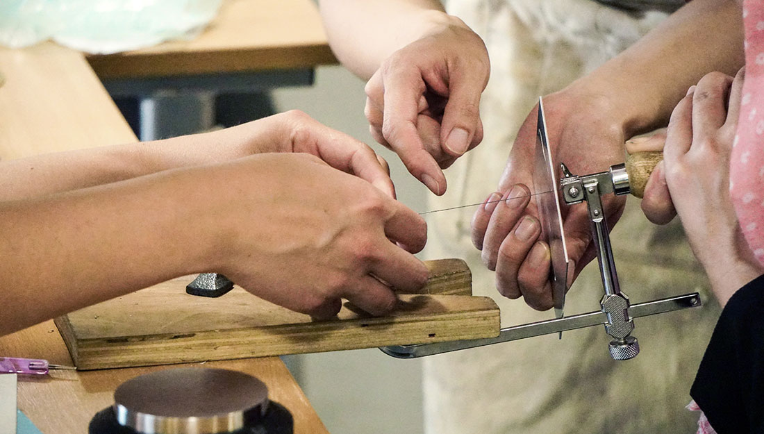 Hands use a piercing saw to cut metal.