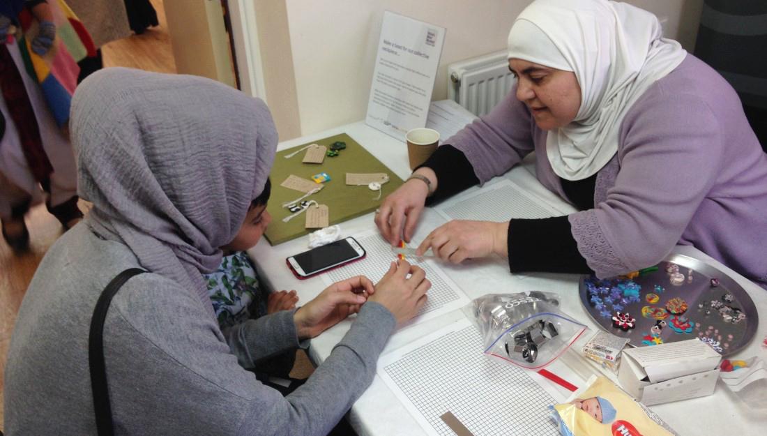 Member of Shelanu helps member of the public make a bead