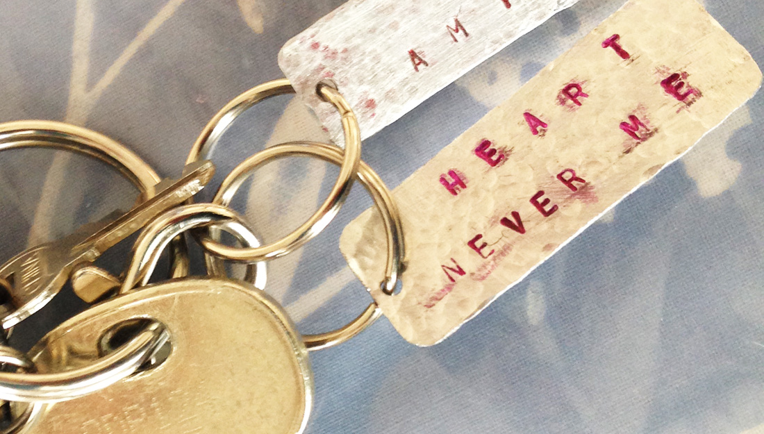 A handmade aluminium key ring with letters stamped on in pink.