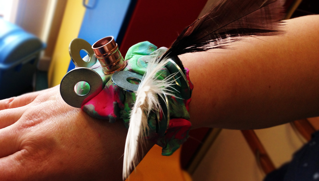 Wrist adornment made with feathers, fabric, copper tubing and washers on a wrist.