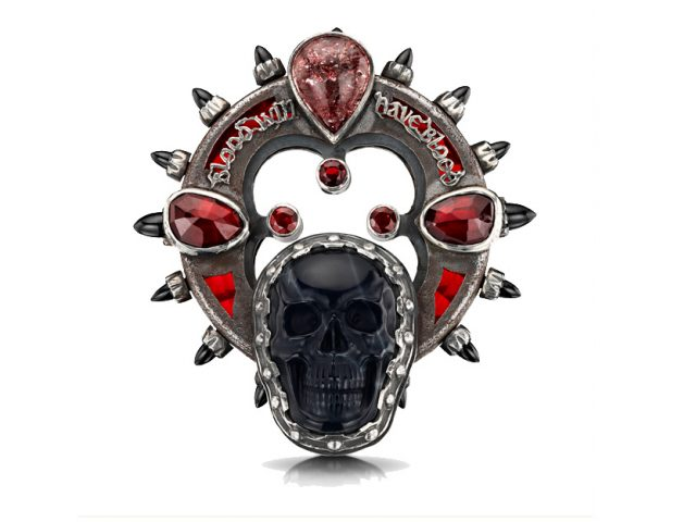 An elaborate brooch featuring a skull and a quote from Macbeth.