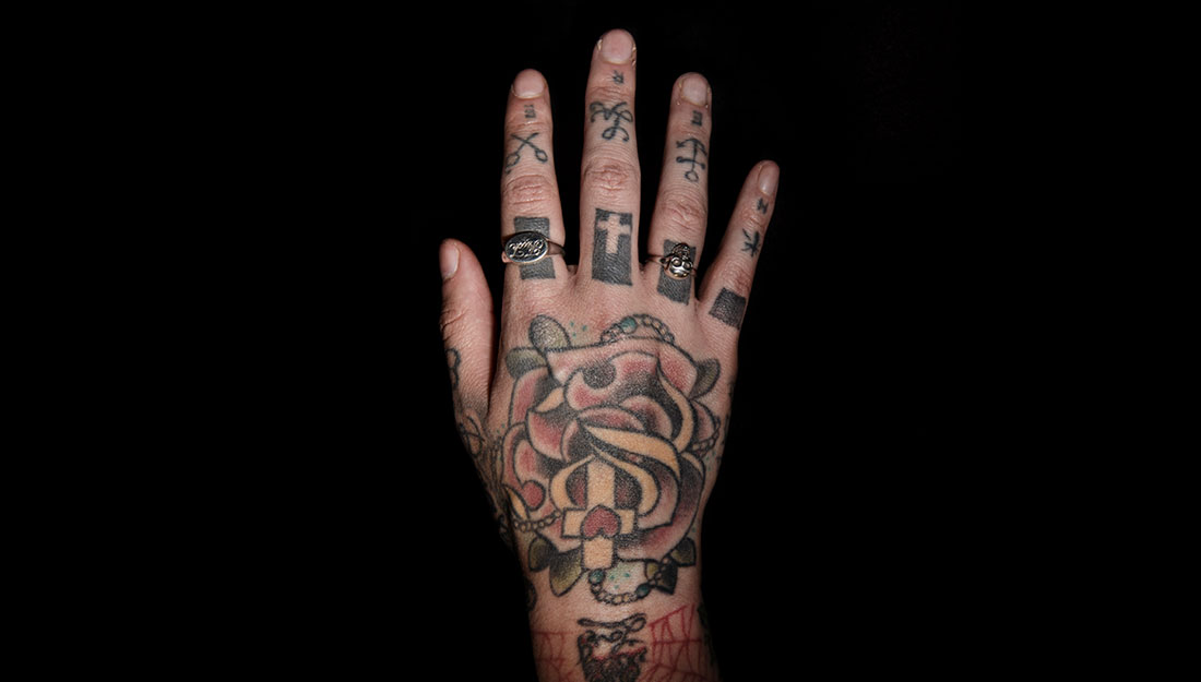 A heavily tattooed hand with rings.