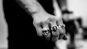 A hand wearing rings designed with skull motifs.