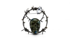 A metal brooch designed with motifs of barbed wire and a skull.