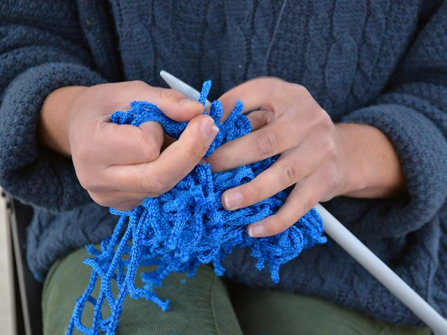 A pair of hands use a knitting needle to knit blue cord.