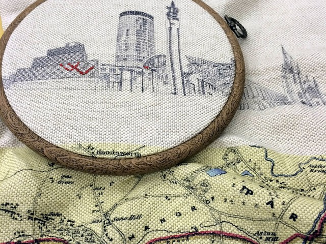 The main sights of Birmingham printed onto material placed in an embroidery hoop, red thread is embroidered into it.