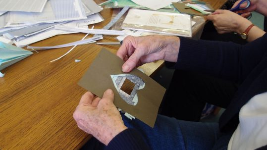 An older lady learns how to make a card from paper.
