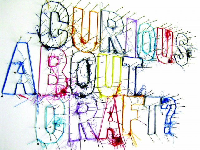 words created by wrapping brightly coloured thread around pins which are hammered into a white board.