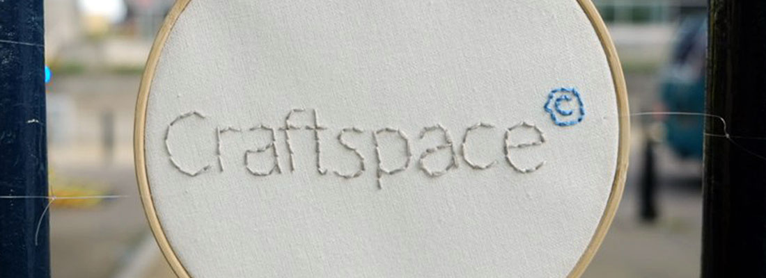 The Craftspace logo stitched into white cloth on an embroidery hoop.