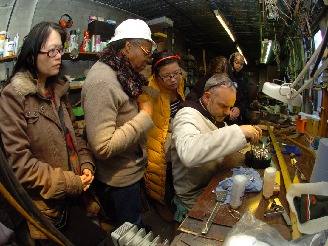 A group of women watch a jewellery maker at his workbench.