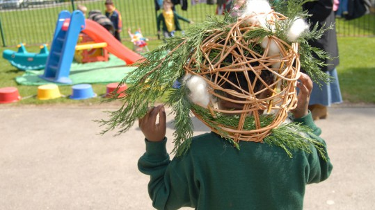 A young child places a small woven willow sculpture onto his head.