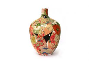 A vase is reformed from broken pieces covered in bright fabric and stiched back together.