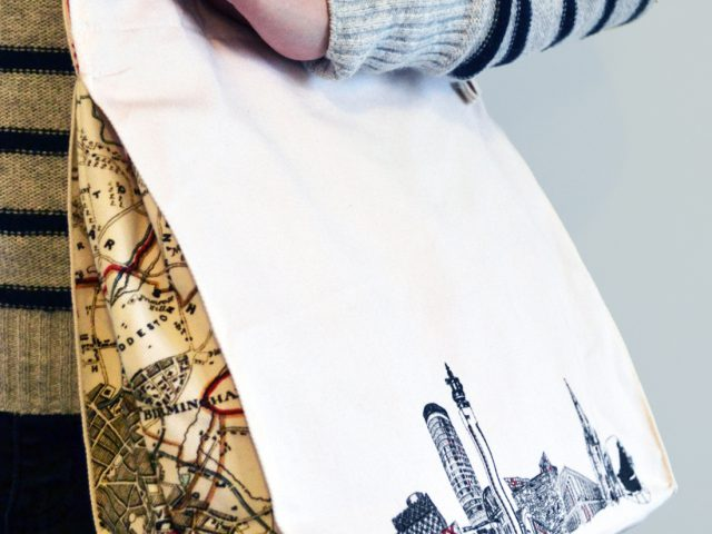 A young woman wears the bag over her shoulder. It is simple in design with a black and white line drawing of the skyline and red trimmings.